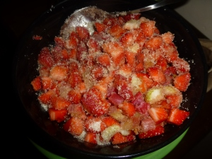 Macerating the strawberries and rhubarb with sugar and vanilla.